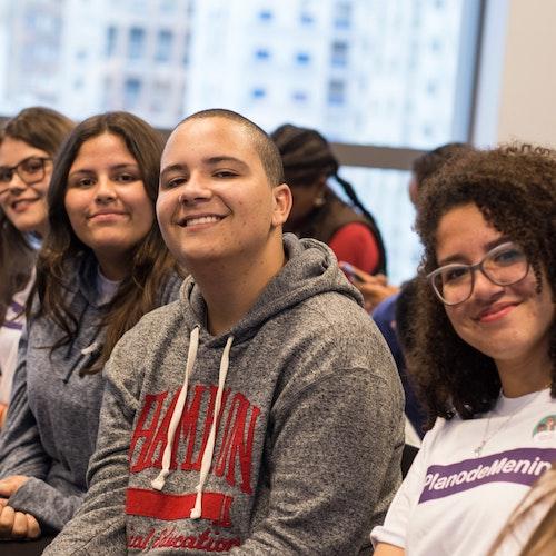 4 人的合影,他们都坐着,其中一名男孩坐在其他女孩中间,大家都面对镜头微笑