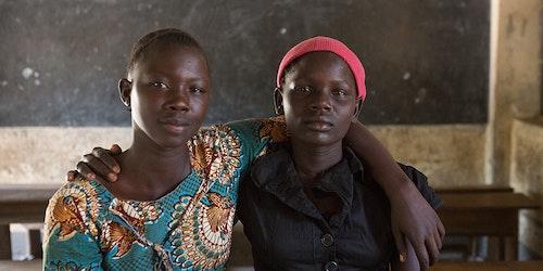 两名乌干达女孩在教室里彼此挽着胳膊,对着镜头微笑