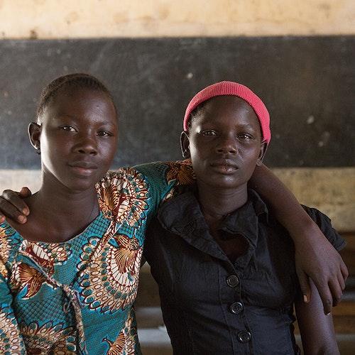 deux filles ougandaises se tenant la main et souriant face à la caméra dans la salle de classe