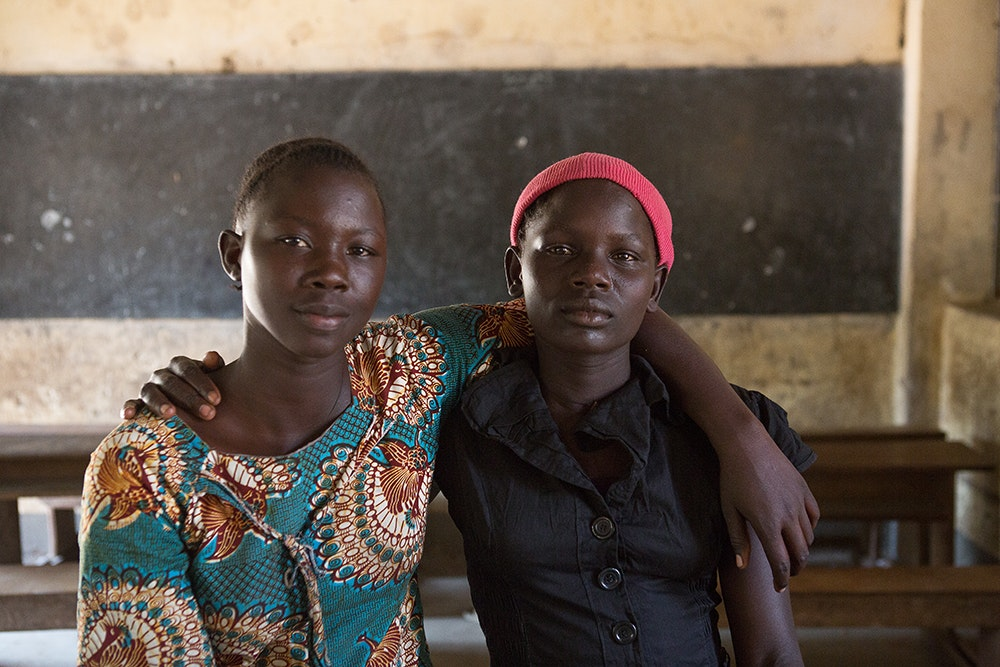 two Uganda girls with hand on each other's arm and smile to the camera inside the classroom