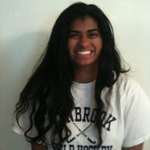 Aditi Pradhan, Cidade natal: San Jose, Califórnia, 2011-2012, segundo grupo de consultoras adolescentes (foto de rosto em close, sem nitidez). Uma adolescente sorridente olhando para a câmera, tendo um plano de fundo branco. Ela está usando uma camiseta de hóquei branca