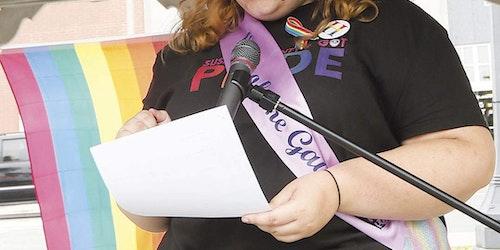 """(半身照)Zoe Heath 穿着印有""""pride""""的 T 恤,右手拿着一张纸,站在麦克风前讲话"""