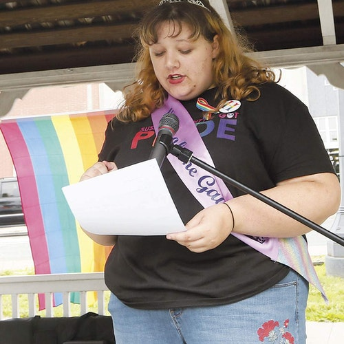 (half body hot) Zoe Heath with her pride shirt and right hand holding a paper and speaking in front of the standing microphone
