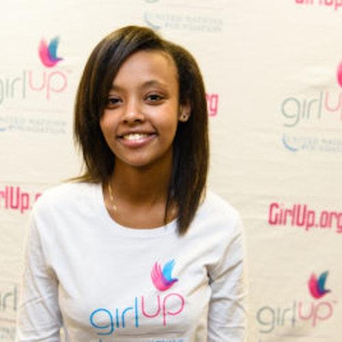 """Alesiya Dejene, consultora adolescente de 2013-2014 (foto de perto, um pouco desfocada). Uma adolescente sorridente olhando para a câmera, tendo uma parede com """"girlup.org"""" no plano de fundo. Ela está usando a camiseta toda branca da Girl Up"""