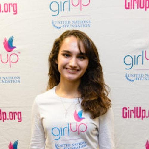 """Alex Leone, consultora adolescente de 2013-2014 (foto de perto, um pouco desfocada). Uma adolescente sorridente olhando para a câmera, tendo uma parede com """"girlup.org"""" no plano de fundo. Ela está usando a camiseta toda branca da Girl Up"""