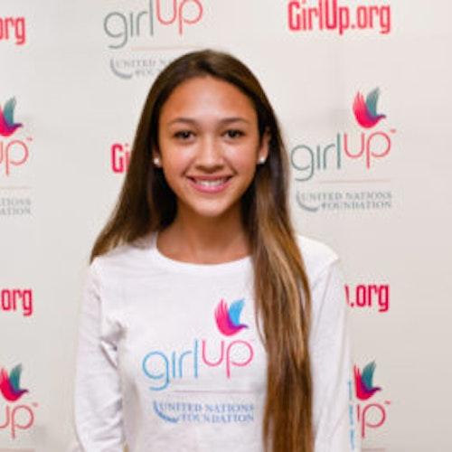 """Alexa Brewster, consultora adolescente de 2012-2013 (foto de perto, um pouco desfocada). Uma adolescente sorridente olhando para a câmera, tendo uma parede com """"girlup.org"""" no plano de fundo. Ela está usando a camiseta toda branca da Girl Up"""