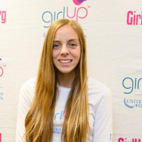 """Alexis Kallen, consultora adolescente de 2013-2014 (foto de perto, um pouco desfocada). Uma adolescente sorridente olhando para a câmera, tendo uma parede com """"girlup.org"""" no plano de fundo. Ela está usando a camiseta toda branca da Girl Up"""