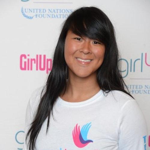 """Amy Gong Liu, consultora adolescente de 2014-2015 (foto de perto). Uma adolescente sorridente olhando para a câmera, tendo uma parede com """"girlup.org"""" no plano de fundo. Ela está usando a camiseta toda branca da Girl Up"""