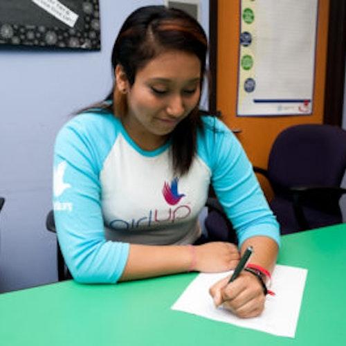 Angie Partida, da classe fundadora de consultoras adolescentes (foto de perto, sem nitidez). Uma adolescente sorrindo e olhando para baixo, segurando uma caneta em cima do caderno, tendo um escritório como plano de fundo. Ela está usando a camiseta branca de manga comprida azul da Girl Up