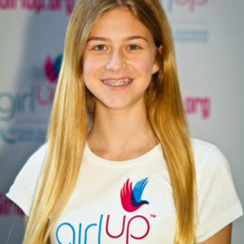 """Annie Gersh, consultora adolescente de 2011-2012 (foto de perto, um pouco desfocada). Uma adolescente sorridente olhando para a câmera, tendo uma parede com """"girlup.org"""" no plano de fundo. Ela está usando a camiseta toda branca da Girl Up"""