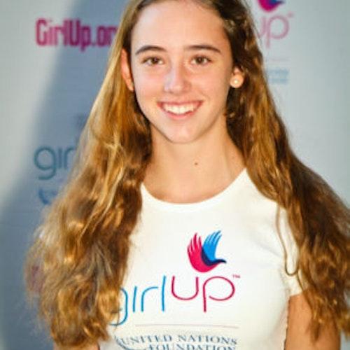 """Annie Kiyonga, Cidade natal: Chevy Chase, Maryland, 2011-2012, segundo grupo de consultoras adolescentes (foto de perto). Uma adolescente sorridente olhando para a câmera, tendo uma parede com """"girlup.org"""" no plano de fundo. Ela está usando a camiseta toda branca da Girl Up"""