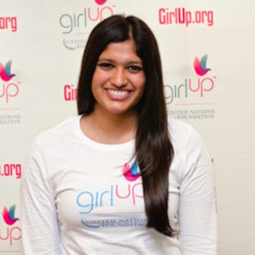 """Archana Somasegar, consultora adolescente de 2012-2013 (foto de perto, um pouco desfocada). Uma adolescente sorridente olhando para a câmera, tendo uma parede com """"girlup.org"""" no plano de fundo. Ela está usando a camiseta toda branca da Girl Up"""