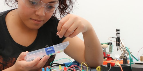 a girl wearing lab glasses and testing electricity on the table