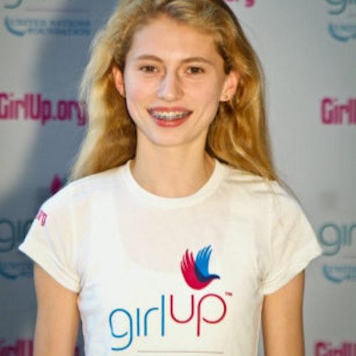 """Avery McCall, Cidade natal: Winnetka, Illinois, 2011-2012, segundo grupo de consultoras adolescentes (foto de perto). Uma adolescente sorridente olhando para a câmera, tendo uma parede com """"girlup.org"""" no plano de fundo. Ela está usando a camiseta toda branca da Girl Up"""