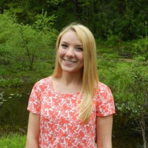 Becca Bean, consultora adolescente de 2016-2017 (foto de meio-corpo, desfocada), sorridente olhando para a câmera, tendo o verde das plantas como plano de fundo