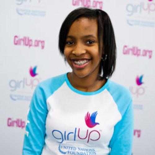 """Bridget Duru, da classe fundadora de consultoras adolescentes (foto de perto, sem nitidez). Uma adolescente sorridente olhando para a câmera, tendo uma parede com """"girlup.org"""" no plano de fundo. Ela está usando a camiseta branca de manga comprida azul da Girl Up"""