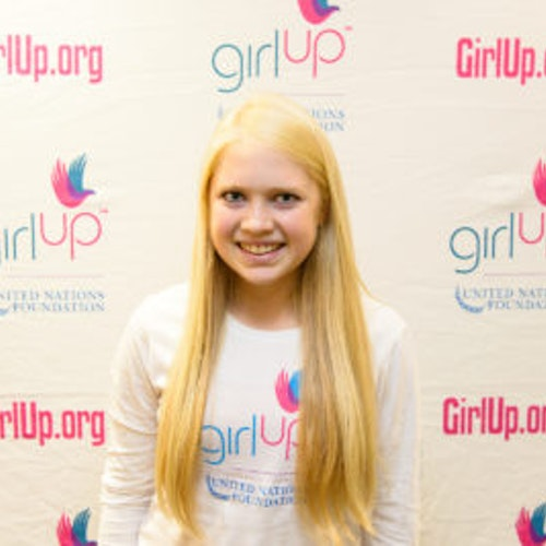 """Carly Bandt, consultora adolescente de 2013-2014 (foto de perto, um pouco desfocada). Uma adolescente sorridente olhando para a câmera, tendo uma parede com """"girlup.org"""" no plano de fundo. Ela está usando a camiseta toda branca da Girl Up"""