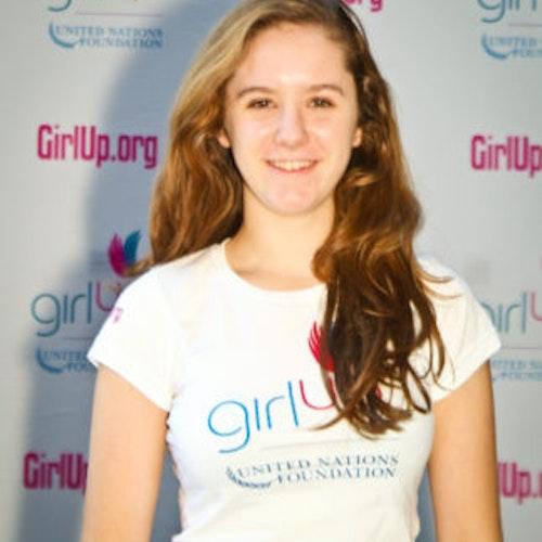 """Charlotte May, Cidade natal: Bronxville, Nova York, 2011-2012, segundo grupo de consultoras adolescentes (foto de perto). Uma adolescente sorridente olhando para a câmera, tendo uma parede com """"girlup.org"""" no plano de fundo. Ela está usando a camiseta toda branca da Girl Up"""