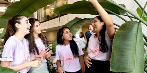 Cuatrochicas de GirlUp hablando entre sí y riendo.