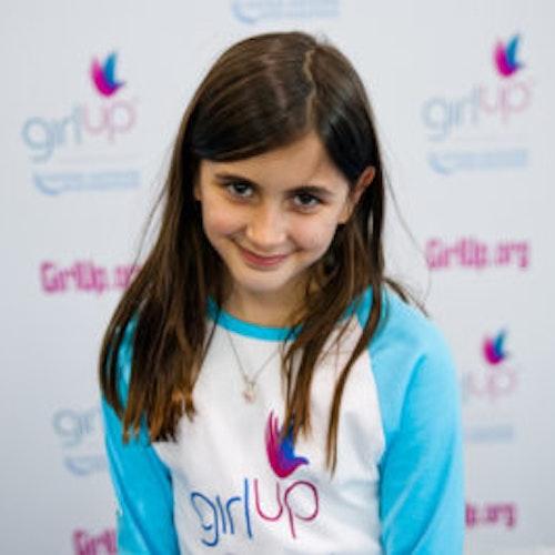 """Darya Pishevar, do grupo fundador de consultoras adolescentes (foto de perto, sem nitidez). Uma adolescente sorridente olhando para a câmera, tendo uma parede com """"girlup.org"""" no plano de fundo. Ela está usando a camiseta branca de manga comprida azul da Girl Up"""