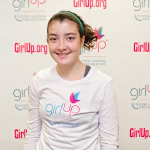 """Delia Friel, consultora adolescente de 2012-2013 (foto de perto, um pouco desfocada). Uma adolescente sorridente olhando para a câmera, tendo uma parede com """"girlup.org"""" no plano de fundo. Ela está usando a camiseta toda branca da Girl Up"""