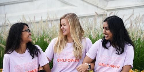 3 名不同种族的女孩穿着印有 Girl Power 的粉色 T 恤,笑着看向彼此