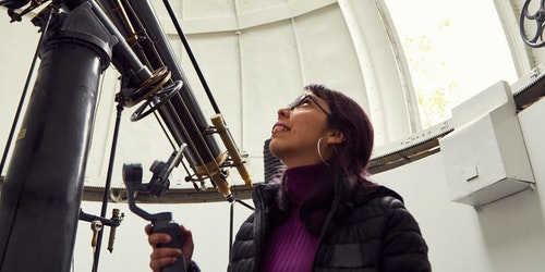 a woman looking up and holding the huge telescope