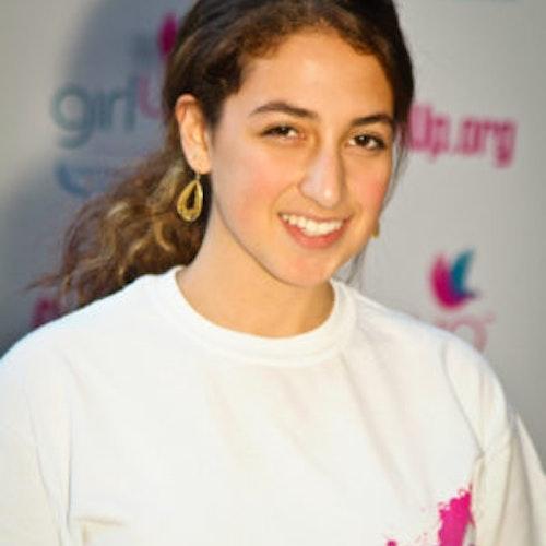 """Eliora Katz, Cidade natal: Washington, capital dos EUA, 2011-2012, segundo grupo de consultoras adolescentes (foto de perto). Uma adolescente sorridente olhando para a câmera, tendo uma parede com """"girlup.org"""" no plano de fundo. Ela está usando a camiseta toda branca da Girl Up"""