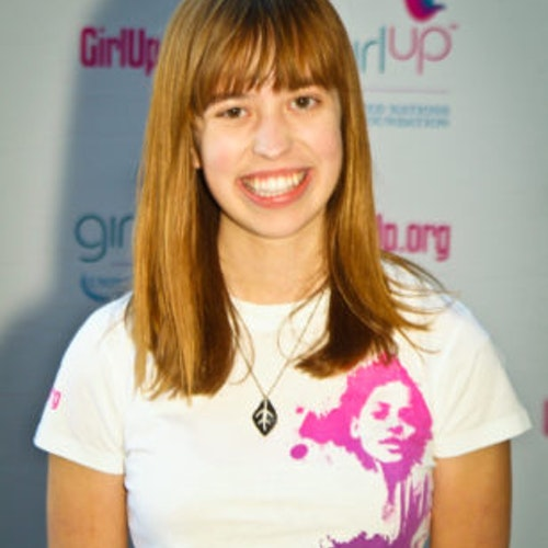 """Emily Harwell, consultora adolescente de 2011-2012 (foto de perto). Uma adolescente sorridente olhando para a câmera, tendo uma parede com """"girlup.org"""" no plano de fundo. Ela está usando a camiseta toda branca da Girl Up"""