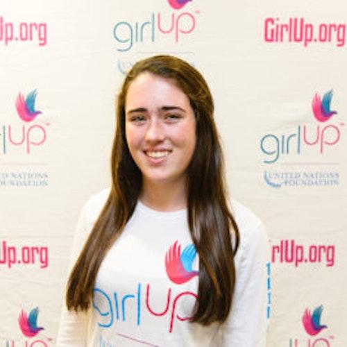 """Emma Knoll, consultora adolescente de 2013-2014 (foto de perto, um pouco desfocada). Uma adolescente sorridente olhando para a câmera, tendo uma parede com """"girlup.org"""" no plano de fundo. Ela está usando a camiseta toda branca da Girl Up"""