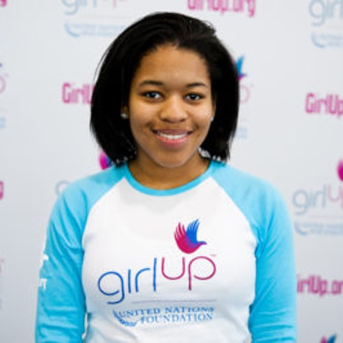 """Erica Lamberson, do grupo fundador de consultoras adolescentes (foto de rosto em close, sem nitidez). Uma adolescente sorridente olhando para a câmera, tendo uma parede com """"girlup.org"""" no plano de fundo. Ela está usando a camiseta branca de manga comprida azul da Girl Up"""