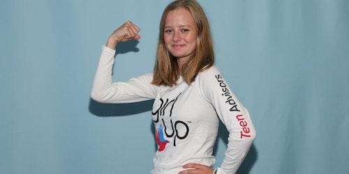 Eva, Jeune conseillère (portant son maillot GirlUp), adoptant la pose de Superwoman pour le Sommet (arrière-plan bleu)