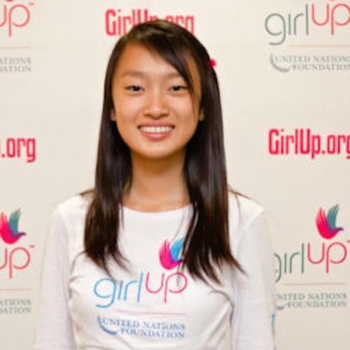 """Eva (YingYing) Shang, consultora adolescente de 2012-2013 (foto de perto, um pouco desfocada). Uma adolescente sorridente olhando para a câmera, tendo uma parede com """"girlup.org"""" no plano de fundo. Ela está usando a camiseta toda branca da Girl Up"""