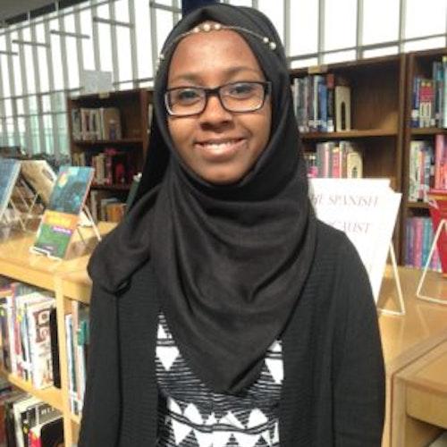 Faatimah Solomon, consultora adolescente de 2016-2017 (foto de meio-corpo, em close), tendo a biblioteca como plano de fundo. Ela está usando um hijab preto
