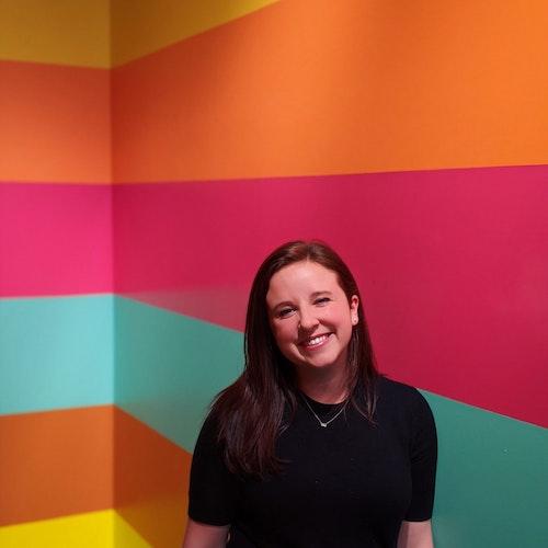 Morgan Wood, coordenadora de programas, em foto de meio-corpo com um plano de fundo colorido