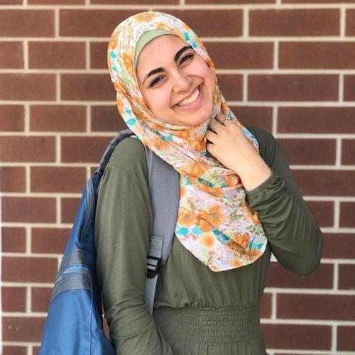 Ganna Omar, consultora adolescente de 2019-2020 (retrato), sorridente olhando para a câmera, usando seu hijab com flores amarelas