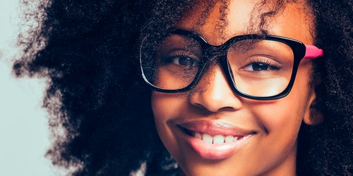 (close cutoff shot) a girl with big glasses on and a big smile
