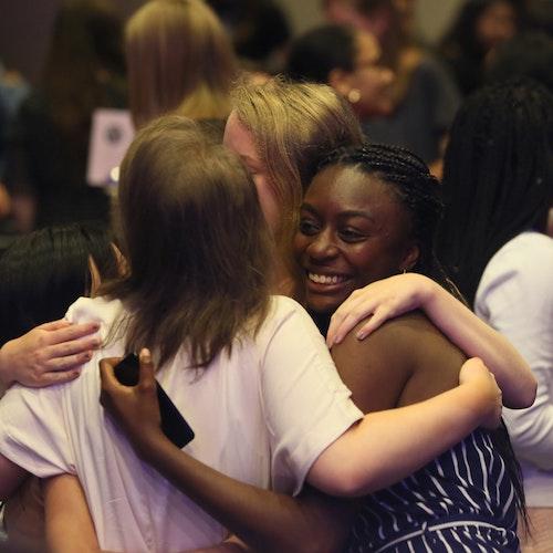 photo de groupe de 4filles de GirlUp de races différentes se serrant dans les bras
