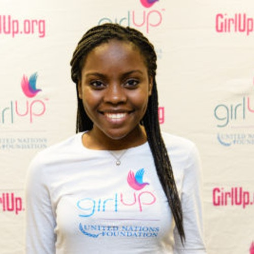 Gloria Samen_2013-2014 Teen Advisor (close angle headshot, a picture little blurry ) a teen girl wearing her girl up white shirt with her smiley face facing the camera, and background is girlup.org board