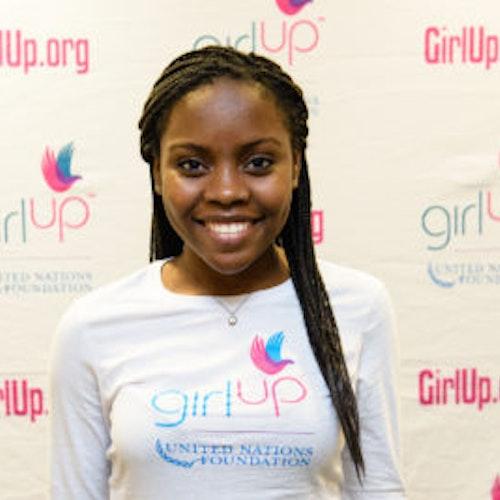 """Gloria Samen, consultora adolescente de 2013-2014 (foto de perto, um pouco desfocada). Uma adolescente sorridente olhando para a câmera, tendo uma parede com """"girlup.org"""" no plano de fundo. Ela está usando a camiseta toda branca da Girl Up"""