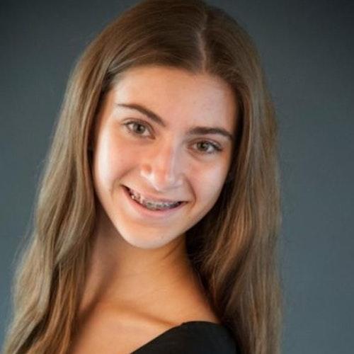 Grace Rabinowitz, consultora adolescente de 2016-2017 (foto tirada na escola, em close), sorridente olhando para a câmera e um plano de fundo cinza