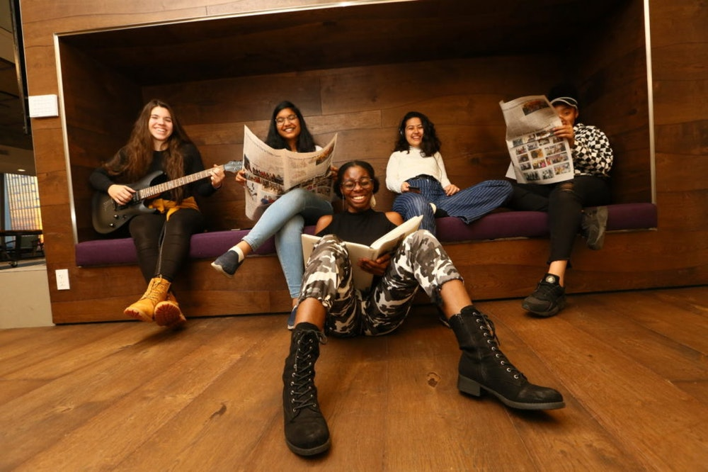(long shot) 5 different ethnic girls in the picture holding books (sitting on the front floor) and holding guitar and newspaper (sitting on the back couch)