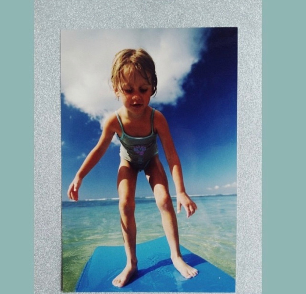 a little girl trying to stand up still on her float board