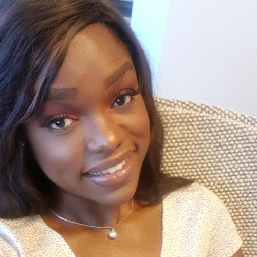 Selfie de Helen-Audrey, auxiliar sênior de finanças, usando um vestido branco