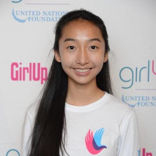 """Janet Ho, consultora adolescente de 2014-2015 (foto de perto). Uma adolescente sorridente olhando para a câmera, tendo uma parede com """"girlup.org"""" no plano de fundo. Ela está usando a camiseta toda branca da Girl Up"""