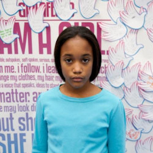 """Jillian Medina, do grupo fundador de consultoras adolescentes (foto perto, sem nitidez). Uma adolescente sorridente olhando para a câmera, tendo uma parede com """"girlup.org"""" no plano de fundo. Ela está usando uma camiseta azul de manga comprida da girl up"""