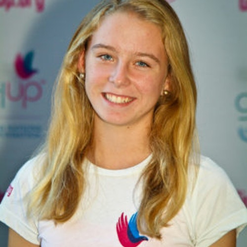 """Jillian Murray, Cidade natal: Chevy Chase, Maryland, 2011-2012, segundo grupo de consultoras adolescentes (foto de perto). Uma adolescente sorridente olhando para a câmera, tendo uma parede com """"girlup.org"""" no plano de fundo. Ela está usando a camiseta toda branca da Girl Up"""