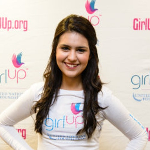"""Julia Sumouske, consultora adolescente de 2013-2014 (foto de perto, um pouco desfocada). Uma adolescente sorridente olhando para a câmera, tendo uma parede com """"girlup.org"""" no plano de fundo. Ela está usando a camiseta toda branca da Girl Up"""