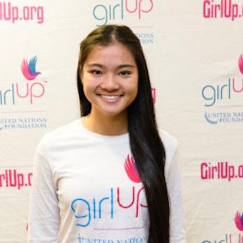 """Kaitlin Hung, consultora adolescente de 2013-2014 (foto de perto, um pouco desfocada). Uma adolescente sorridente olhando para a câmera, tendo uma parede com """"girlup.org"""" no plano de fundo. Ela está usando a camiseta toda branca da Girl Up"""