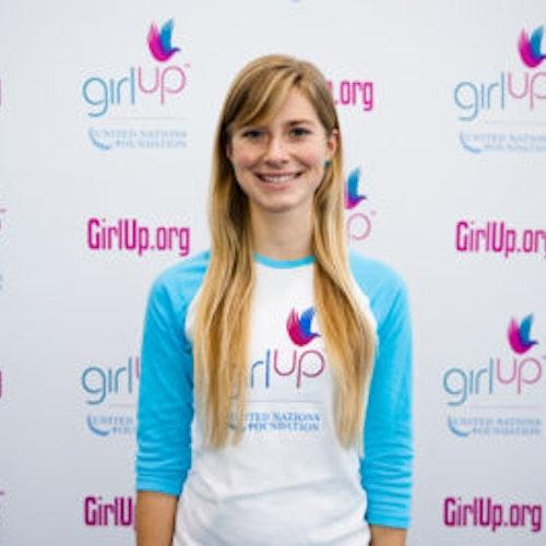 """Karina Jougla, do grupo fundador de consultoras adolescentes (foto de meio-corpo, sem nitidez). Uma adolescente sorridente olhando para a câmera, tendo uma parede com """"girlup.org"""" no plano de fundo. Ela está usando a camiseta branca de manga comprida azul da Girl Up"""